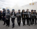 Police advance toward protestors as a store burns, Monday, April 27, 2015, during unrest following the funeral of Freddie Gray in Baltimore. Gray died from spinal injuries about a week after he was arrested and transported in a Baltimore Police Department van.